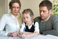 Family helping daughter with homework. Royalty Free Stock Photography