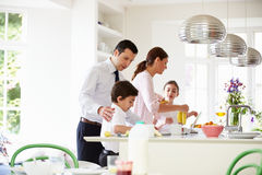 Family Helping To Clear Up After Breakfast Royalty Free Stock Photos
