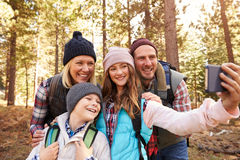 Family on hike in a forest taking selfie group portrait Royalty Free Stock Photos