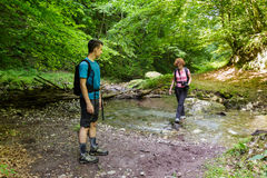 Family of hikers crossing the river Stock Images