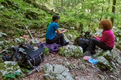 Backpackers having a break from hiking. Family of hikers resting after climbing on a trail Royalty Free Stock Photos