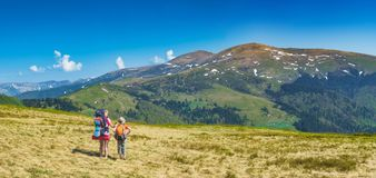 Family of hikers on a trekking day. In a mountain valley. Travel and family concept. Panoramic format Royalty Free Stock Image