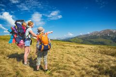 Family of hikers on a trekking day in a mountain valley. The son shows his mother and small sister the peak. Travel and family concept Royalty Free Stock Photos