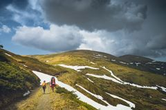 Family hikers walking by the road in a spring mountains Stock Image
