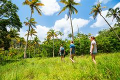 Family hiking. Family of mother and kids hiking on summer day at tropical island stock photo