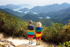 Family hiking in Hong Kong mountains. Family with kids hiking in Hong Kong mountains. Beautiful landscape with hills, sea and city skyscrapers in Hong Kong stock images