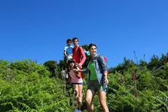 Family hiking in mountains. Family on a hiking day going down hill Stock Photo