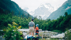 Family hiking in the mountains. A young mother and her son hike together in the mountains on a beautiful summer evening. They look at high-mountain landscape stock photography
