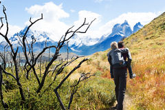 Family hiking in patagonia. Young father giving his son a piggyback ride during active and strenuous hike to mirador condor at torres del paine national park Stock Photos