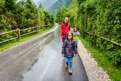 Family hiking on road in nature on a rainy day royalty free stock photo