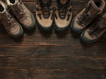Family hiking shoes on dark wooden backgroud. Top view. Travel C. Oncept Stock Photos