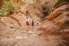 Family hiking together in a sandstone slot canyon near Arches National Park Stock Image