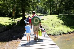 Family on a hiking trip crossing river on the bridge Royalty Free Stock Photos