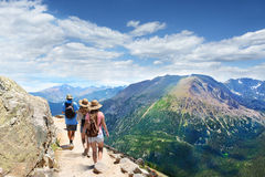 Family on a hiking trip in the mountains. People with backpacks hiking on summer vacation in mountains. Father with his family enjoying time on a trip. Rocky Stock Photo