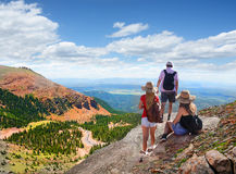 Family on a hiking trip in the mountains. People standing on top of mountain rock. Family looking at beautiful summer mountains landscape,from  Pike National Stock Photos