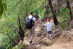 Family hiking. Family of two hiking together the kalalau trail at kauai island, hawaii royalty free stock image