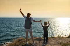 Family at hill peak to see sunset. Happy mom and son raising hands after reaching to mountain summit by hiking. Mother and child looking at sea and sunset on Royalty Free Stock Images