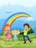 A family at the hilltop and a rainbow in the sky Royalty Free Stock Photos