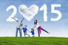 Family hold hands at field under cloud of 2015 Royalty Free Stock Photography