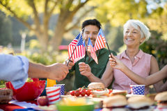 Family holding american flags while having meal in the park. Happy family holding american flags while having meal in the park Stock Photo