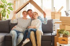 Family holding cardboard roof above their heads royalty free stock image