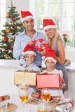Family holding christmas presents. Family wearing santa hats holding christmas presents Royalty Free Stock Photography