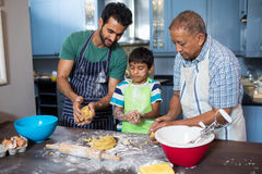 Family holding dough while preparing food. In kitchen at home Royalty Free Stock Photography
