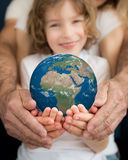 Family holding Earth planet in hands Royalty Free Stock Images