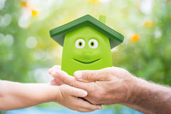 Eco house. Family holding eco cartoon house in hands against green spring background. Environment protection concept Royalty Free Stock Images