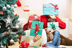 Family holding gifts in front of their faces Royalty Free Stock Photo