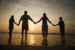 Family Holding Hands on Beach Watching the Sunset. Silhouette of family holding hands on beach watching the sunset. Horizontally framed shot Royalty Free Stock Photography