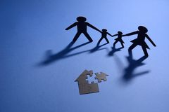 Family holding hands with jigsaw puzzle house Stock Image