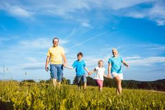 Family holding hands running over meadow stock photo