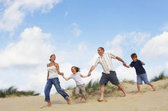 Family Holding Hands And Running On Sand. Full length of a happy family holding hands and running down sand dune on beach Royalty Free Stock Photo
