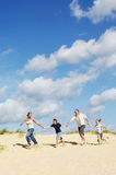 Family Holding Hands And Running On Sand. Full length of a happy family holding hands and running down sand dune on beach Royalty Free Stock Photography