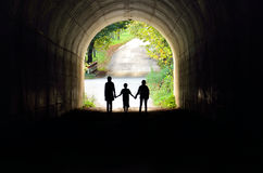 Family holding hands in the tunnel. Family silhouette in back lighting Royalty Free Stock Photo