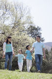 Family holding hands, walking in park. Stock Photos