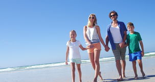 Family holding hands while walking on shore at beach stock video footage