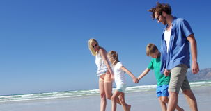 Family holding hands while walking on shore at beach stock video