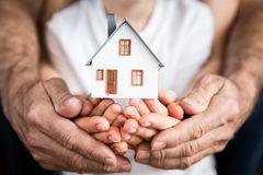 Family holding house in hands. Moving and spring renovation concept Royalty Free Stock Photography