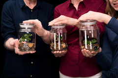 Family holding jars with money Royalty Free Stock Photo