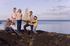 Family holding model sailboat by sea, smiling, portrait, sunset Stock Photos