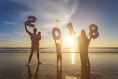 Family holding number balloon 2018 on the beach at the sunset ti Stock Photo