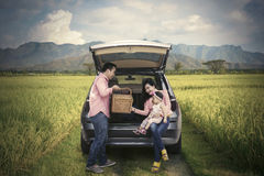 Family holding picnic basket in rice field Stock Photography