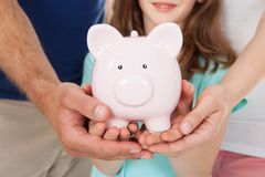 Family holding piggy bank. Midsection of family holding piggy bank together Royalty Free Stock Photo