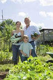 Family Holding Vegetables In Community Garden Stock Photo