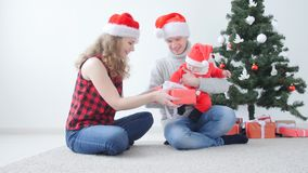 Family holiday and christmas concept. Young mother and father with a child unpack a Christmas present. Indoors stock video