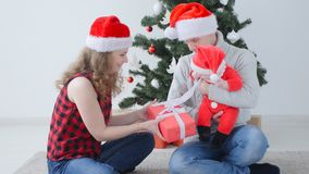 Family holiday and christmas concept. Young mother and father with a child unpack a Christmas present. Indoors stock footage