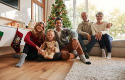 Family holiday gathering by Christmas tree. Portrait of a happy family sitting at home in the living room. Three generations - family holiday gathering by stock images