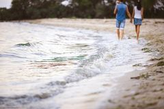 Family holiday near the sea. Two adults in jeans clothes with a child in their arms walk along the sandy beach from behind royalty free stock image